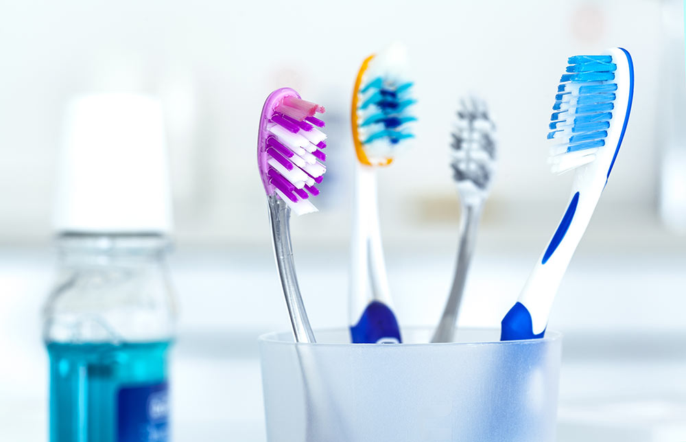 four toothbrushes and mouthwash