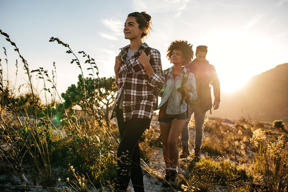 three young adults outside hiking