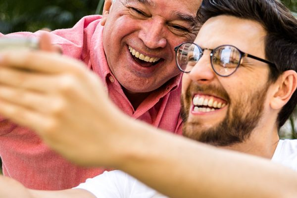 two men smiling and taking a selfie