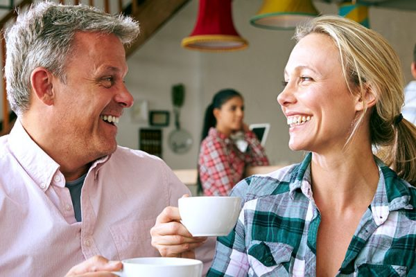 Middle aged man and woman drinking coffee and smiling.