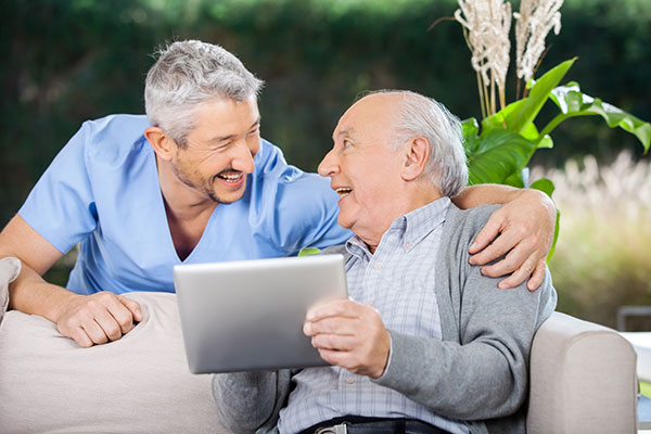 An older man sitting on couch and looking at something with his doctor standing behind him