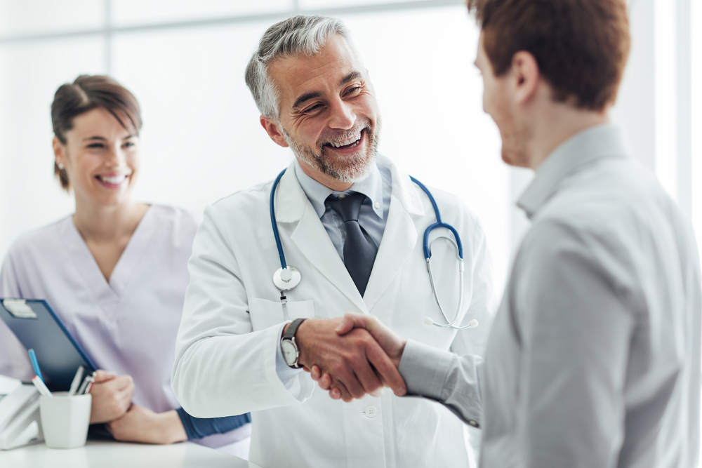 A doctor and a male patient shaking hands